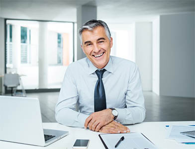 Confident businessman posing at desk