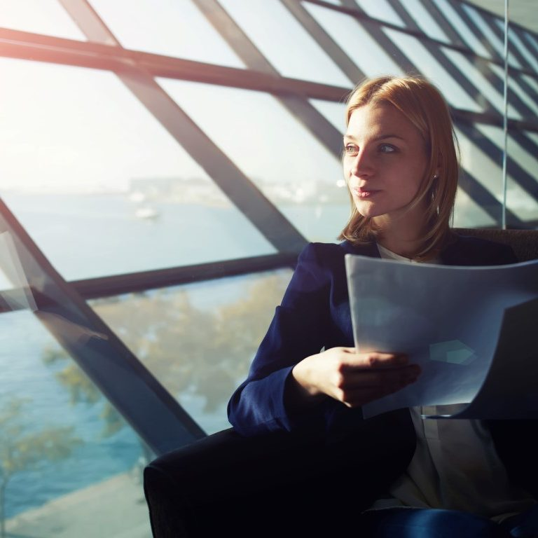 Portrait of young elegant woman sitting in modern office interior holding papers and pensively gazing out of the window, filtered image with flare sun light from the window